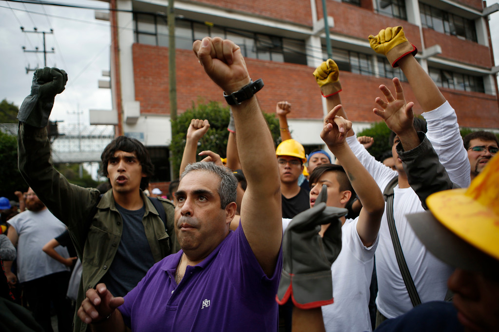 . Volunteers raise their fists asking for silence as they listen to a request for emergency supplies to be taken to another earthquake stricken area, in the Linda Vista neighborhood of Mexico City, Wednesday, Sept. 20, 2017. People by the millions rushed from homes and offices across central Mexico, after a 7.1 earthquake, sometimes watching as buildings they had just fled fell behind them with an eruption of dust and debris. (AP Photo/Rebecca Blackwell)