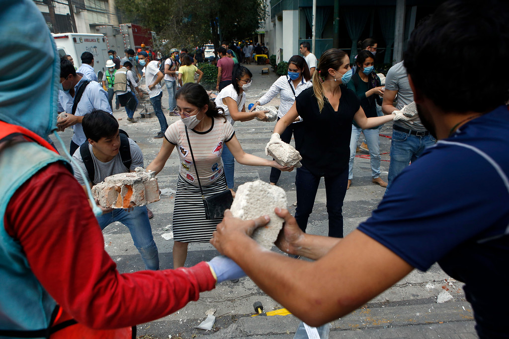 . Volunteers pick up the rubble from a building that collapsed during an earthquake in the Condesa neighborhood of Mexico City, Tuesday, Sept. 19, 2017. Survivors quickly rallied, clambering over grotesque ruins of buildings and joining professional rescue workers to try to save friends, neighbors and strangers. (AP Photo/Rebecca Blackwell)