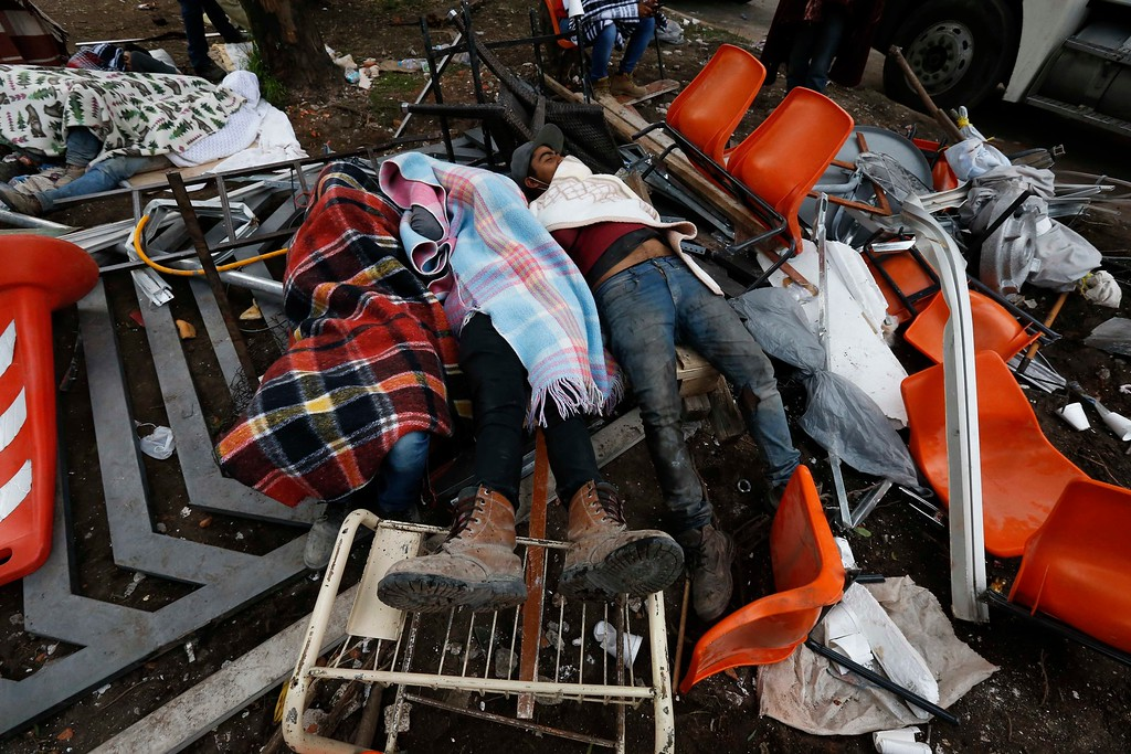 . Rescue workers rest atop a toppled gate and amid debris as others continue the search and rescue efforts at the Enrique Rebsamen school that collapsed after an earthquake in Mexico City, Wednesday, Sept. 20, 2017. One of the most desperate rescue efforts was at this school, where a wing of the three-story building collapsed into a massive pancake of concrete slabs. (AP Photo/Marco Ugarte)