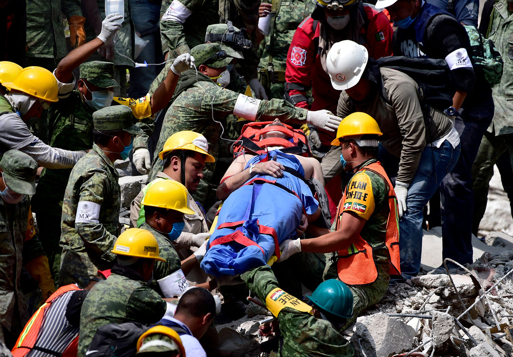 . A survivor is pulled out of the rubble from a flattened building in Mexico City on September 20, 2017 as the search for survivors continues a day after a strong quake hit central Mexico. A powerful 7.1 earthquake shook Mexico City on Tuesday, causing panic among the megalopolis\' 20 million inhabitants on the 32nd anniversary of a devastating 1985 quake. (PEDRO PARDO/AFP/Getty Images)