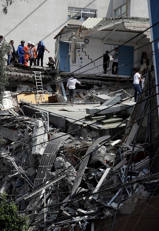 . Rescue workers and volunteers search a building that collapsed after an earthquake in downtown Mexico City, Tuesday, Sept. 19, 2017. A powerful earthquake jolted central Mexico on Tuesday, causing buildings to sway sickeningly in the capital on the anniversary of a 1985 quake that did major damage. (AP Photo/Rebecca Blackwell)