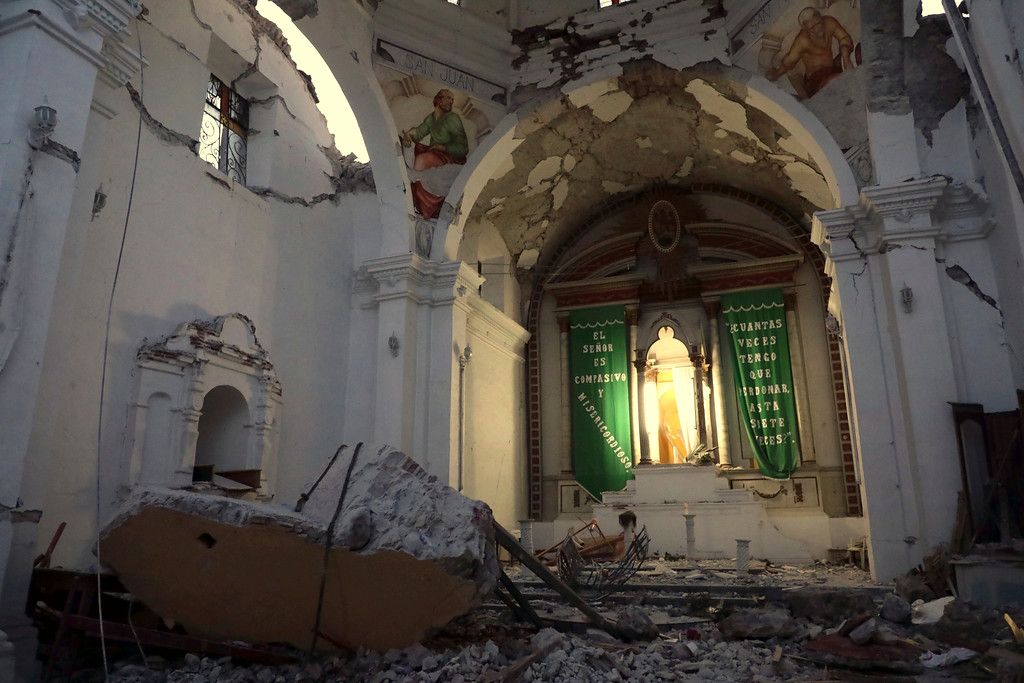 . CORRECTS AGE OF BABY TO TWO MONTHS, NOT TWO YEARS - The sky is exposed from inside Santiago Apostol church which collapsed during the 7.1 earthquake in the town of Atzala in Puebla state, Mexico, Wednesday, Sept. 20, 2017. According to family related to 11 relatives who died inside the church during Tuesday\'s quake, the roof collapsed during a Mass held to baptize a two-month-old girl, and the only people who survived were the baby\'s father, the priest and the priest\'s assistant. (AP Photo/Pablo Spencer)