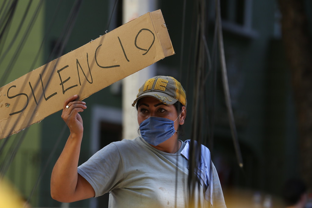 ". A woman holds a sign the reads in Spanish ""Silence\"" as first responders work on removing the rubble of a collapsed building looking for survivors trapped underneath, after a 7.1 earthquake in Mexico City, Tuesday, Sept. 19, 2017.  The earthquake stunned central Mexico, killing more than 100 people as buildings collapsed in plumes of dust.  (AP Photo/Gustavo Martinez Contreras)"