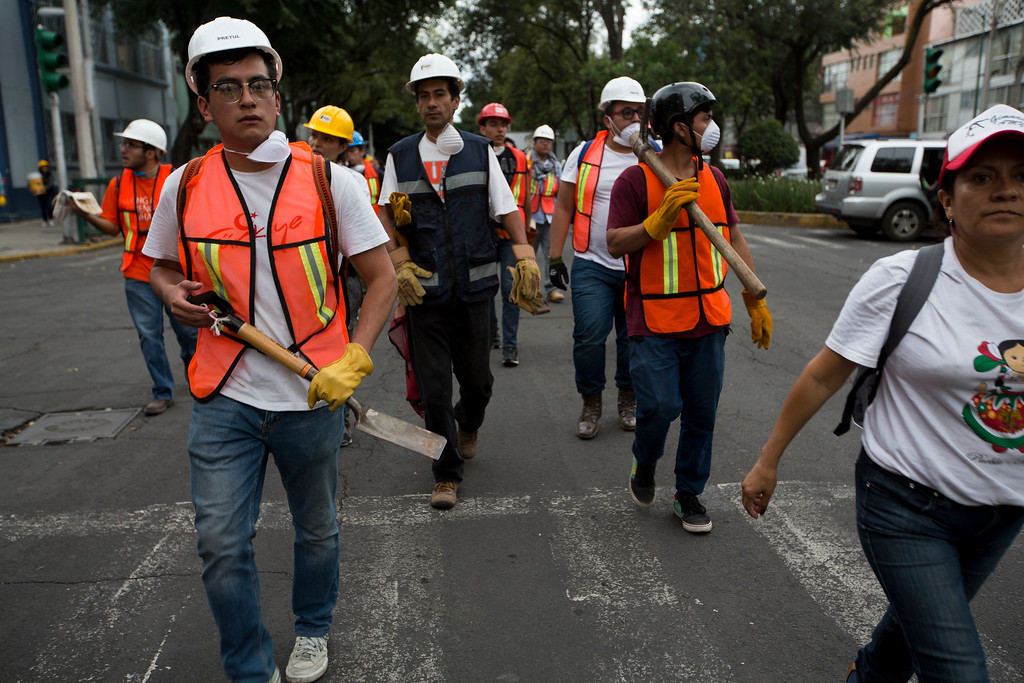 . Rescue volunteers walk to work on a collapsed building, a day after a devastating 7.1 earthquake, in the Del Valle neighborhood of Mexico City, Wednesday, Sept. 20, 2107. Efforts continue at the scenes of dozens of collapsed buildings, where firefighters, police, soldiers and civilians continue their search to reach the living. (AP Photo/Moises Castillo)