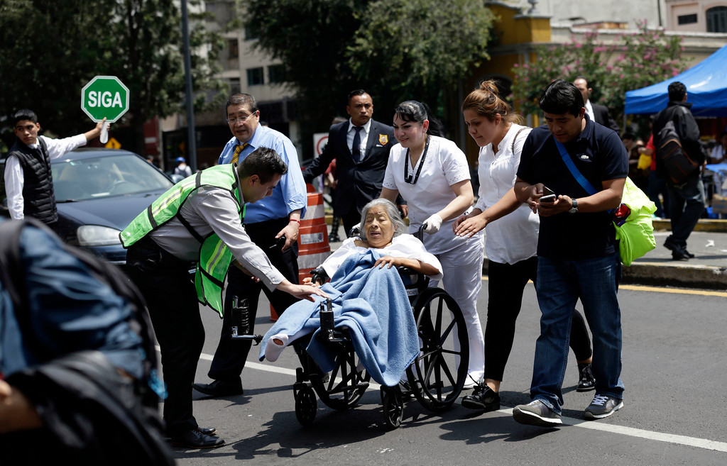 . A woman in a wheelchair is evacuated from a clinic as people gather along Paseo de la Reforma Avenue after an earthquake in Mexico City, Tuesday Sept. 19, 2017. A powerful earthquake jolted central Mexico on Tuesday, causing buildings to sway sickeningly in the capital on the anniversary of a 1985 quake that did major damage. (AP Photo/Marco Ugarte)