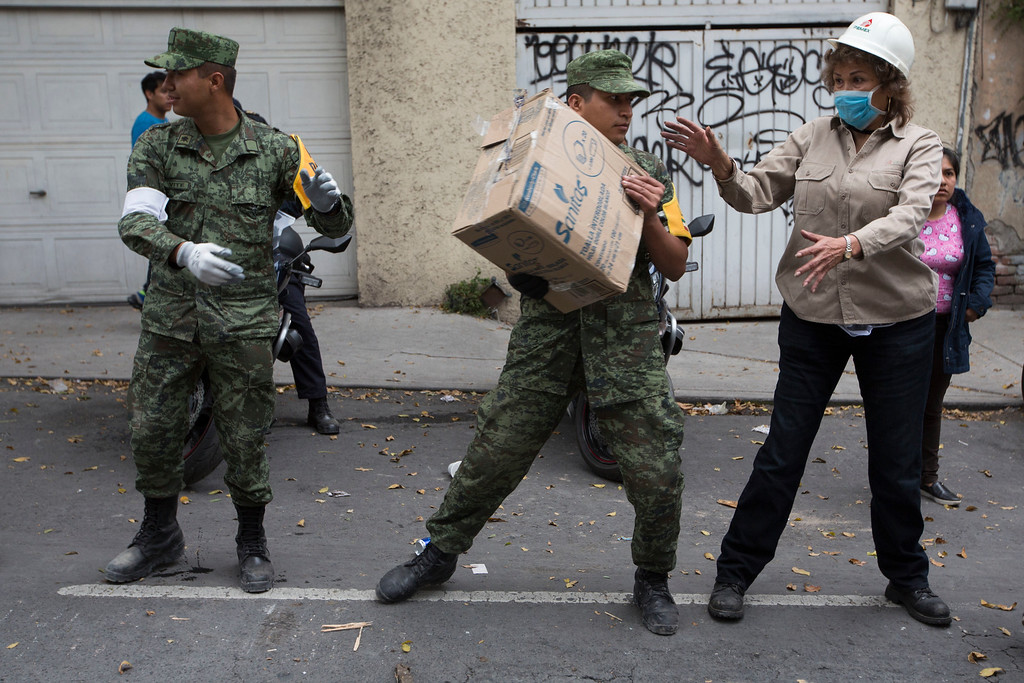 . Soldiers and volunteers receive emergency supplies in the Del Valle neighborhood of Mexico City, Wednesday, Sept. 20, 2017. Efforts continue at the scenes of dozens of collapsed buildings, where firefighters, police, soldiers and civilians continue their search to reach the living. (AP Photo/Moises Castillo)