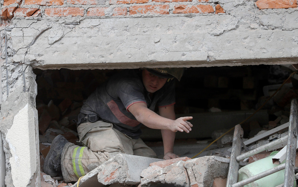 . A rescue worker searches for a trapped survivor at the site of a high rise apartment building of which the first four floors collapsed, in the Linda Vista neighborhood of Mexico City, Wednesday, Sept. 20, 2017. People by the millions rushed from homes and offices across central Mexico, after a 7.1 earthquake, sometimes watching as buildings they had just fled fell behind them with an eruption of dust and debris. (AP Photo/Rebecca Blackwell)