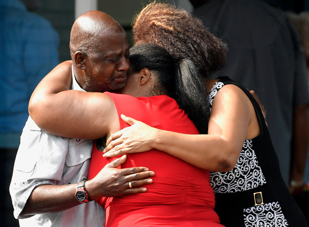 . Leshea White and Kimberly Stallworth hug their uncle Roger Bracey, who was at Burnette Chapel Church of Christ when shots were fired, Sunday, Sept. 24, 2017, in Antioch, Tenn. They were reunited at another nearby church. (Andrew Nelles/The Tennessean via AP)