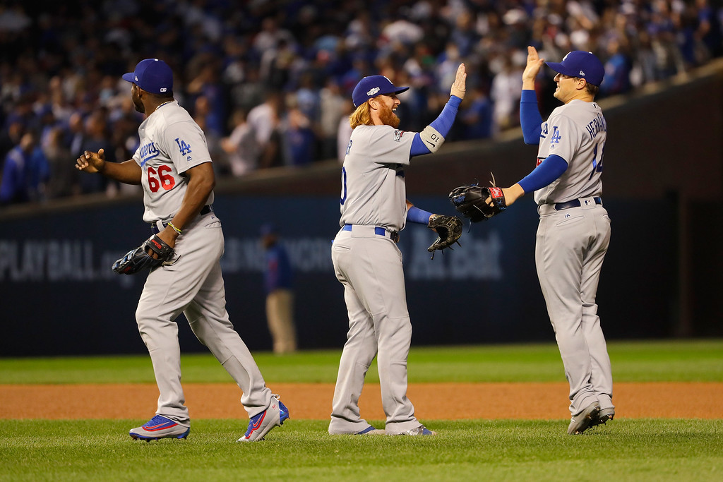 . CHICAGO, IL - OCTOBER 16:  (L-R) Yasiel Puig #66, Justin Turner #10 and Enrique Hernandez #14 of the Los Angeles Dodgers celebrate after defeating the Chicago Cubs 1-0 in game two of the National League Championship Series at Wrigley Field on October 16, 2016 in Chicago, Illinois.  (Photo by Jamie Squire/Getty Images)