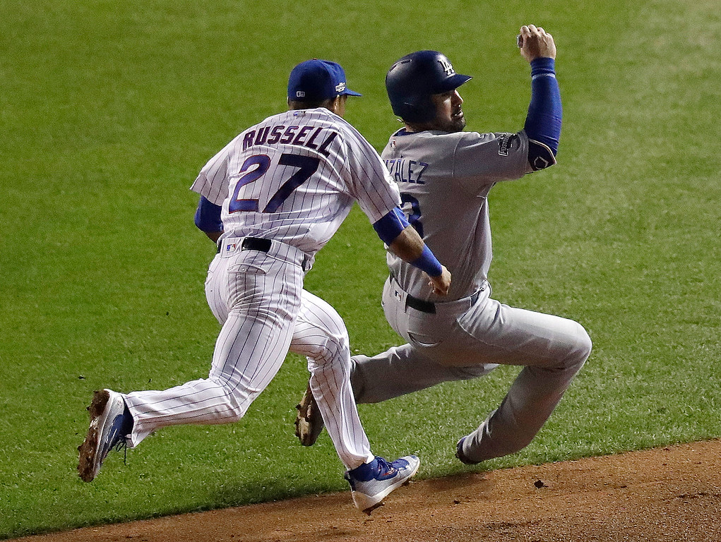 . Chicago Cubs shortstop Addison Russell (27) tags out Los Angeles Dodgers\' Adrian Gonzalez (23) between second and third bases during the sixth inning of Game 2 of the National League baseball championship series Sunday, Oct. 16, 2016, in Chicago. (AP Photo/Charles Rex Arbogast)