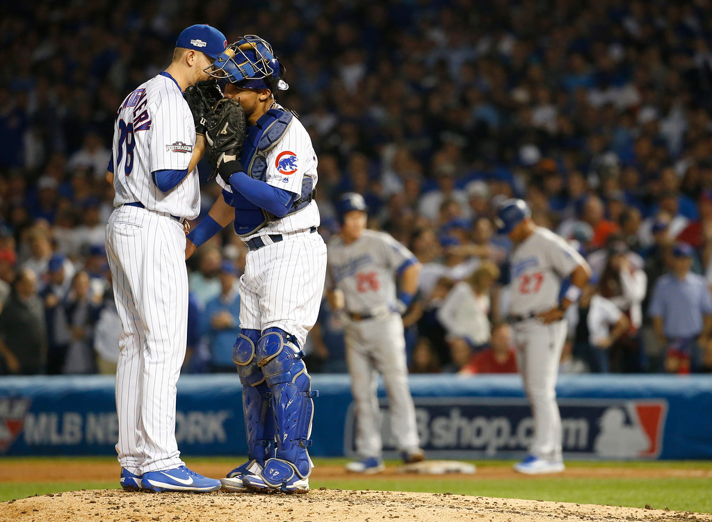 . Chicago Cubs relief pitcher Mike Montgomery, left, talks to catcher Willson Contreras during the seventh inning of Game 2 of the National League baseball championship series against the Los Angeles Dodgers, Sunday, Oct. 16, 2016, in Chicago. (AP Photo/Nam Y. Huh)