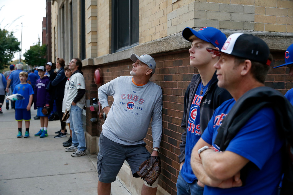 . Mo Mullins, third from right, along with other Chicago Cubs fans, also known as ballhawks, wait for batting practice home run balls on the streets outside Wrigley Field before Game 2 of the National League baseball championship series between the Chicago Cubs and the Los Angeles Dodgers, Sunday, Oct. 16, 2016, in Chicago. (AP Photo/Charles Rex Arbogast)