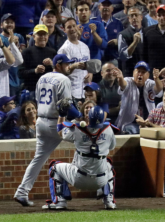 . Los Angeles Dodgers catcher Yasmani Grandal (9) drops a foul ball hit by Chicago Cubs\' Ben Zobrist during the seventh inning of Game 2 of the National League baseball championship series Sunday, Oct. 16, 2016, in Chicago. (AP Photo/Charles Rex Arbogast)
