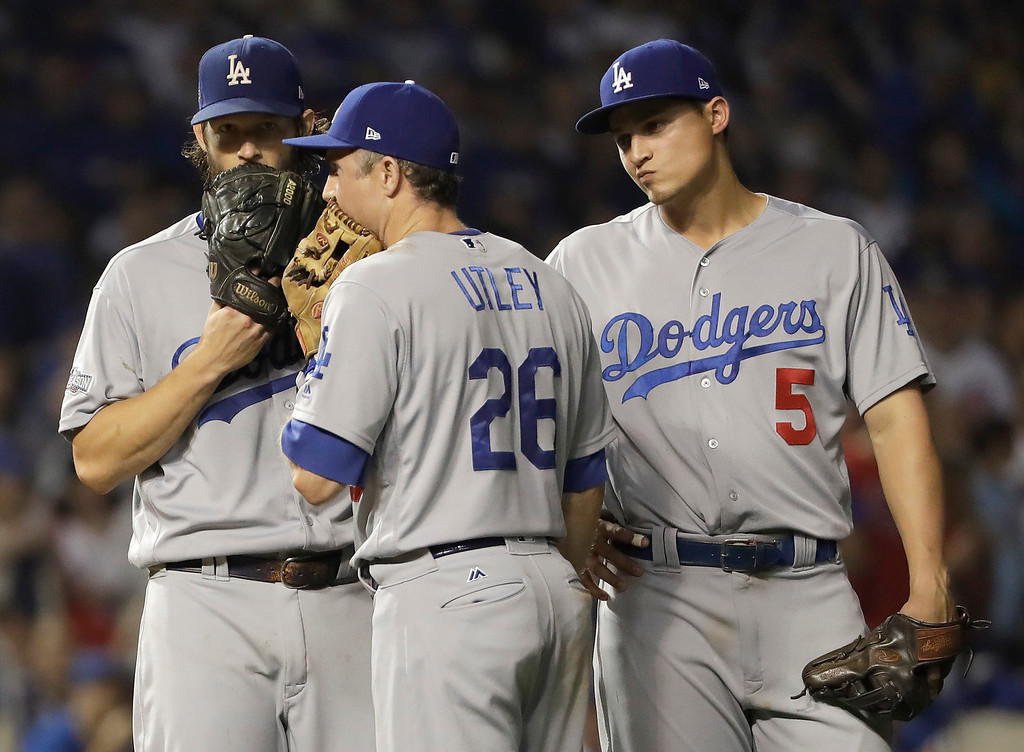 . Los Angeles Dodgers starting pitcher Clayton Kershaw (22) talks to Chase Utley (26) and Corey Seager (5) during the seventh inning of Game 2 of the National League baseball championship series against the Chicago Cubs, Sunday, Oct. 16, 2016, in Chicago. (AP Photo/David J. Phillip)