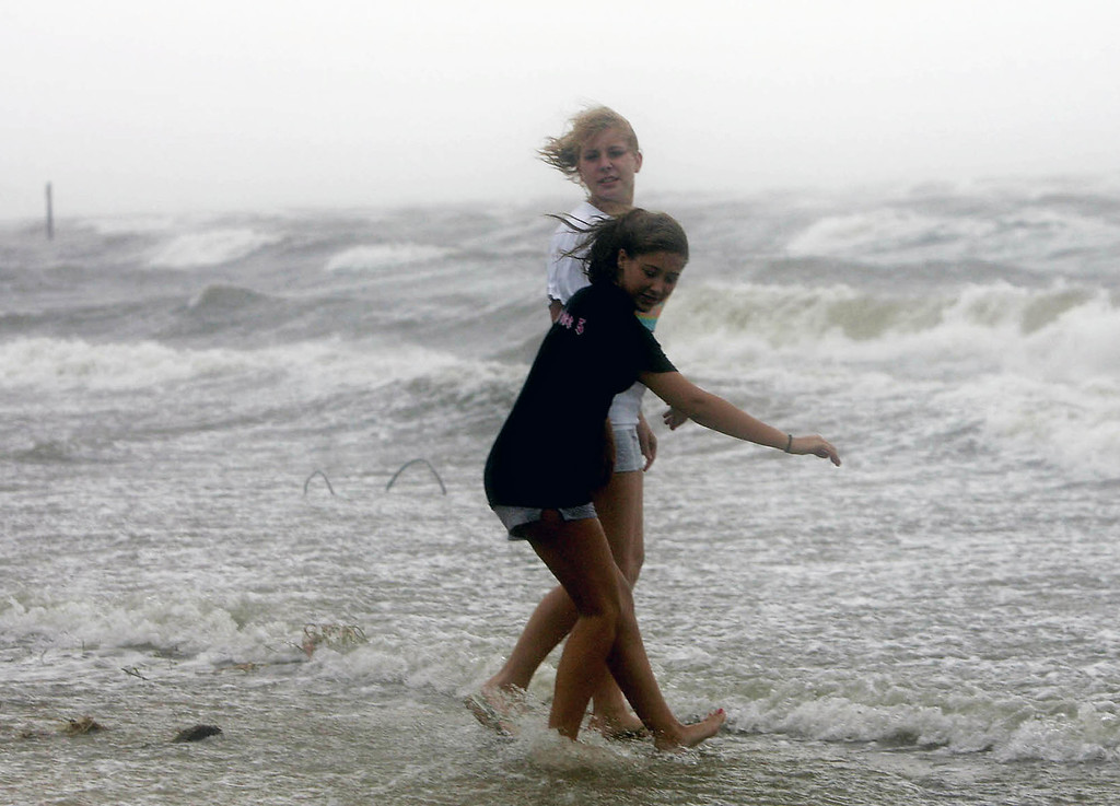 . Sarah Vornholt, front, and Aarica Stone frolic in the surf of Grande Lagoon in Pensacola, Fla. as the outer bands of Hurricane Katrina pass through the area Monday, Aug. 29, 2005.(AP Photo/Peter Cosgrove)