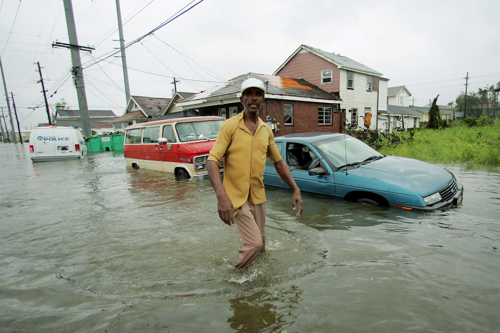 . Elbert Curtis of New Orleans walks through floodwaters that surround his home in New Orleans on Monday, Aug. 29, 2005. Hurricane Katrina dumped torrential rain and did extensive damage to Louisiana and Mississippi. (AP Photo/Dave Martin)