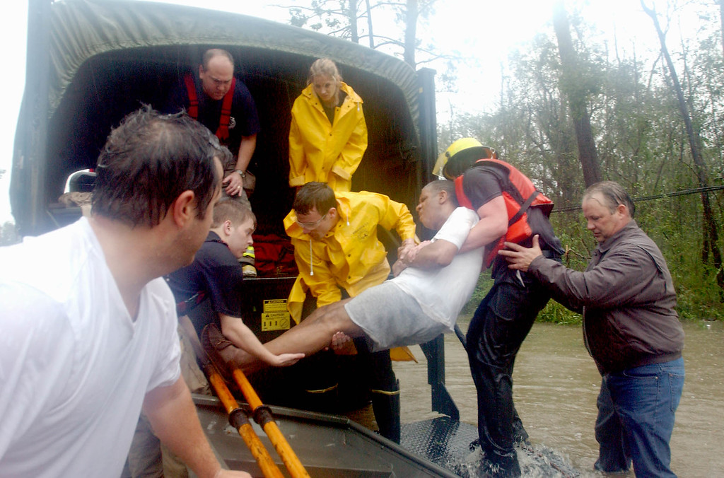 . Parish Councilman Joe Impastato (front left) firemen Robert Artigue, Dana Hall, Gary Artigue, Dan Flynn, Mark Frosch and a good semeritan help .... after he was evacuated from his flooded home in Lacombe, La. on Monday Aug. 29, 2005. (AP Photo/Mari Darr~Welch)