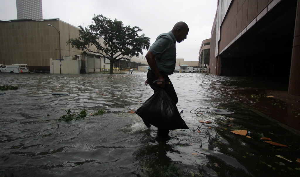 . Arnold James carries a small bag of belongings through floodwaters as he tries to make his way on foot to the Louisiana Superdome in New Orleans, Monday, Aug. 29, 2005, after the roof on James\'s home blew off, forcing him to seek shelter at the Superdome. (AP Photo/Dave Martin)