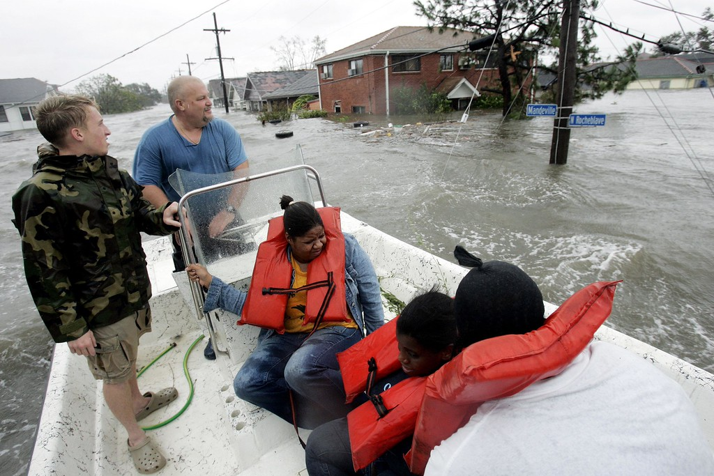 . St. Berard Parish deputy sheriff Jerry Reyes, center, uses his boat to rescue residents after Hurricane Katrina hit the area causing flooding in their New Orleans neighborhood,  Monday Morning, Aug. 29,  2005. Officials called for a mandatory evacuation of the city, but many resident remained in the city.  (AP Photo/Eric Gay)