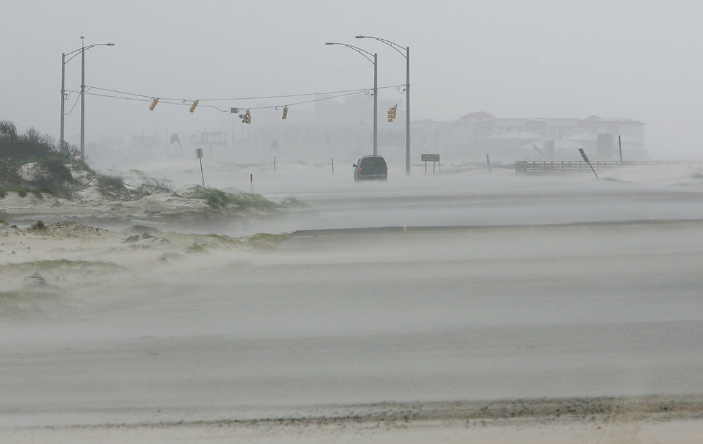 . Sand covers the road leading from Gulf Shores to Orange Beach, Ala., as a police vehicle patrols the area Monday, Aug. 29, 2005 in Orange Beach, Ala.     (AP Photo/Rob Carr)
