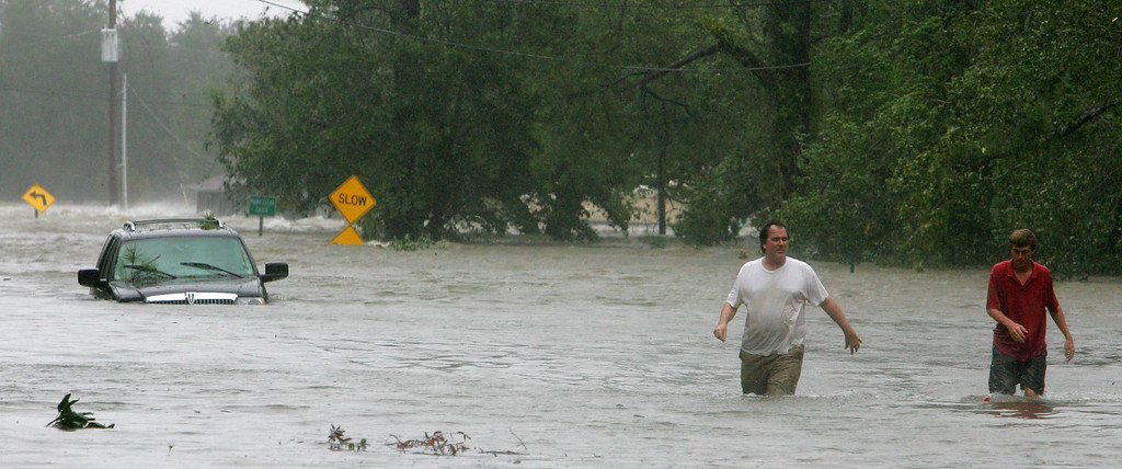 . Eric Leath, left, and Max Haines walk through the flooded streets of Point Clear, Ala., Monday Aug. 29, 2005. Haines, the assistant harbor master at the Marriott Grand Hotel, was checking on boats in the harbor.   (AP Photo/Rob Carr)