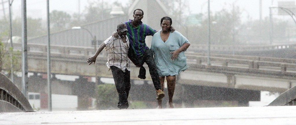. Sammuel Dunn, center is helped to safety by friends after he was rescued by a boat after his home flooded when hurricane Katrina hit in New Orleans,  Monday, Aug. 29,  2005. Officials called for a mandatory evacuation of the city, but many resident remained in the city.  (AP Photo/Eric Gay)