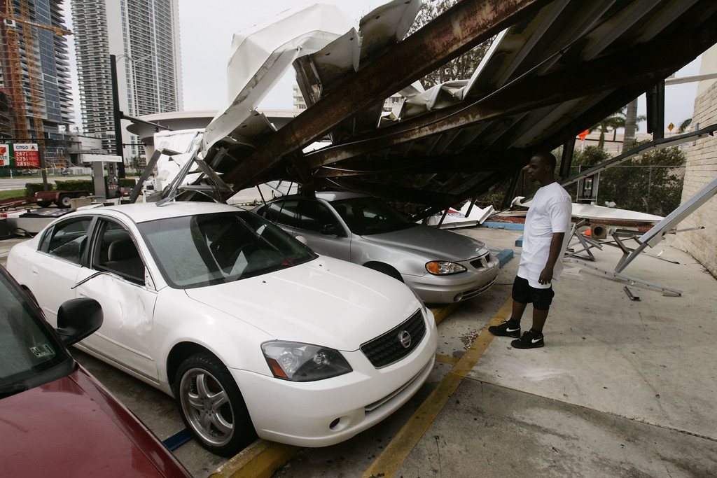 . Shon Toussaint looks at his storm damaged car parked in the lot of the Hallande Beach, Fla. convience store where he works early Friday, Aug. 26, 2005. Hurricane Katrina flooded streets, darkened homes and felled trees as it plowed across South Florida before emerging over the Gulf of Mexico early Friday.  (AP Photo/J. Pat Carter)
