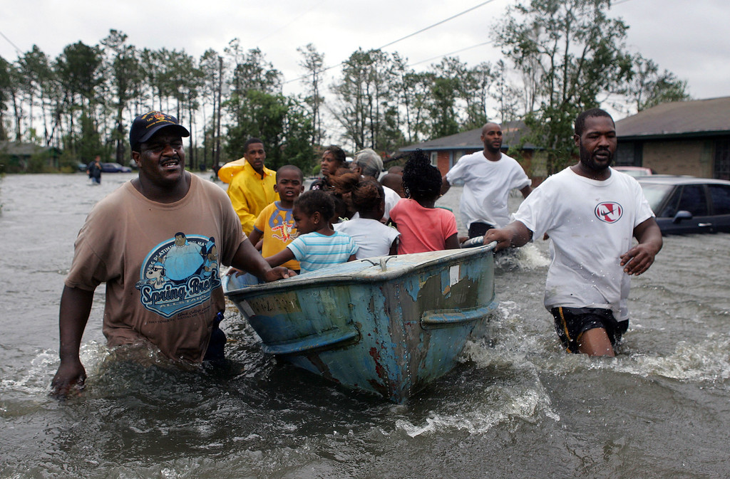. Rescuers use an old row boat to evacuate children and an elderly woman from their flooded homes in Gulfport, Miss., after  Hurricane Katrina struck the Gulf Coast Monday,  Aug. 29, 2005.  (AP Photo/John Bazemore)