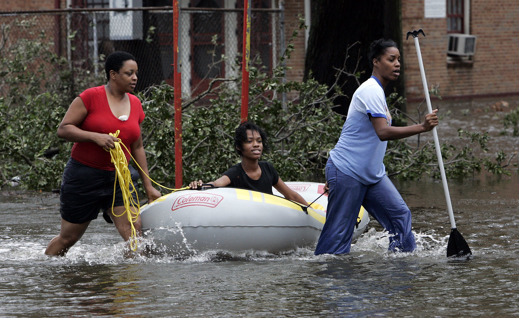 . New Orleans residents Sharon Parker, left, helps her niece Kristan Parker, center, and her sister Kristan\'s mother Wanda Parker use a small boat to negotiate floodwaters near their home after Hurricane Katrina made landfall, dumping torrential rain and bringing 140mph winds with it. (AP Photo/Bill Haber)