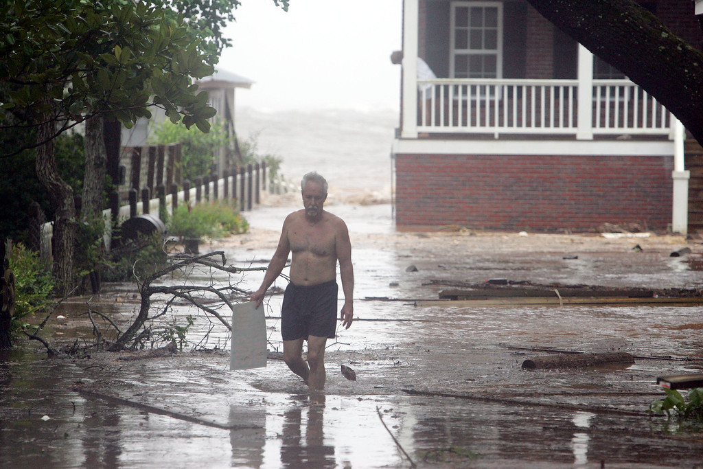 . Fred Wright picks up debris at his house as his wife Carol watches the waves from Mobile Bay break into their backyard  Monday Aug. 29, 2005 in Fairhope, Ala. (AP Photo/Rob Carr)