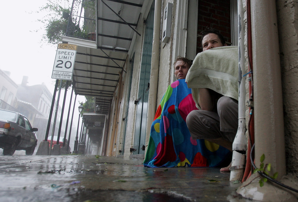 . Blair Quintana, right, and Patrick Lampano seek shelter in a doorway in the French Quarter of New Orleans as Hurricane Katrina pounds the Crescent City on Monday, Aug. 29, 2005. (AP Photo/Dave Martin)