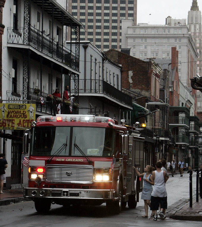 . A New Orleans fire truck cruises down Bourbon Street in the French Quarter as tourists look at damage to the Crescent City on Monday, Aug. 29, 2005. Hurricane Katrina pounded the city with 140 mph winds after it made landfall. (AP Photo/Bill Haber)