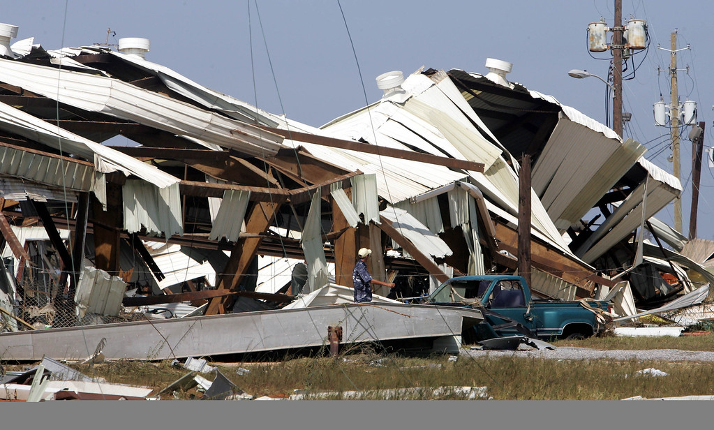 . A man walks past a marina that was ripped apart by Hurricane Katrina, Tuesday Aug. 30, 2005 in Bayou La Batre, Ala. (AP Photo/Rob Carr)