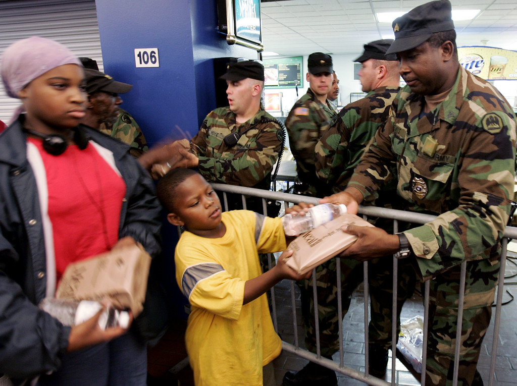 . Members of the National Guard hand out ready-to-eat meals to some of the thousands of displaced residents from Hurricane Katrina at the Superdome, a last-resort shelter, in New Orleans about midnight, Sunday, Aug. 28, 2005. Officials called for a mandatory evacuation of the city, but many residents remained in the city.  (AP Photo/Eric Gay)