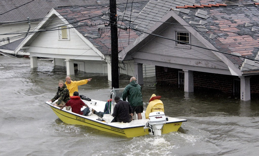 . St. Berard Parish deputy sheriff Jerry Reyes uses his boat to rescue residents after Hurricane Katrina hit the area  causing flooding in their New Orleans neighborhood,  Monday Morning, Aug. 29,  2005. Officials called for a mandatory evacuation of the city, but many resident remained in the city.  (AP Photo/Eric Gay)