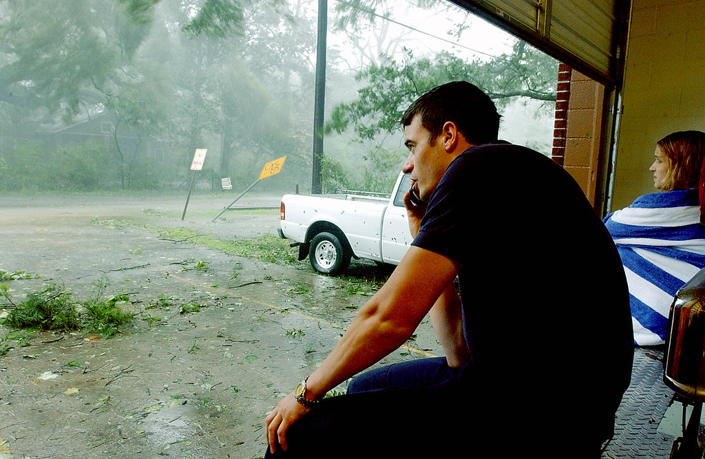 . St. Tammany Parish District 3 Fire Station firefighters Danny Flynn and Dana Hall watch from the Lacombe, La. station as the winds from Hurricane Katrina reach a peak on Monday Aug. 29, 2005. (AP Photo/Mari Darr~Welch)