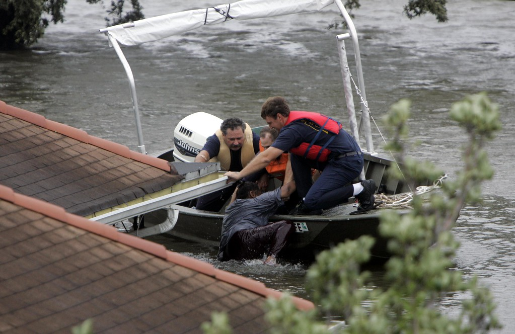. Firefighters rescue a woman from her 9th Ward home after Hurricane Katrina passed through New Orleans, Monday, Aug. 29, 2005. (AP Photo/Dallas Morning News, Michael Ainsworth)
