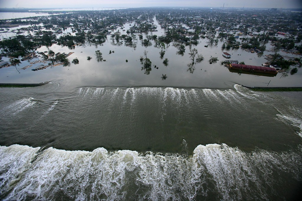 . FILE - In this Aug. 30, 2005 file photo, floodwaters from Hurricane Katrina pour through a levee along Inner Harbor Navigational Canal near downtown New Orleans, La., a day after Katrina passed through the city. (AP Photo/Vincent Laforet, Pool, File)