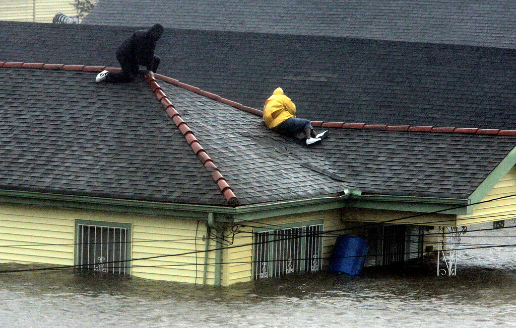 . Bryan Vernon and Dorothy Bell take refuge on their roof top as  Hurricane Katrina hits, causing flooding in their New Orleans neighborhood,  Monday Morning, Aug. 29,  2005. Officials called for a mandatory evacuation of the city, but many resident remained in the city.  (AP Photo/Eric Gay)