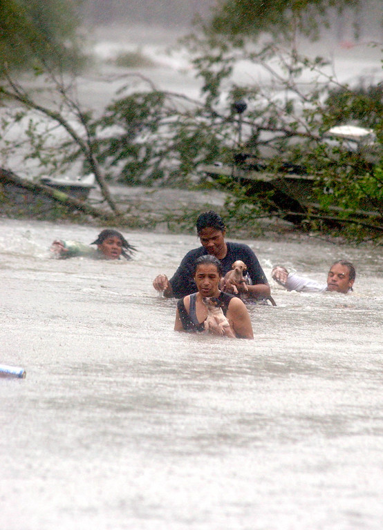 . Lacombe residents Adeline Perkins, Lynell Batiste, Kewanda Batiste, and Ulysses Batiste swim through the flood waters of Hurricane Katrina from their Lacombe, La. home on Monday, Aug. 29, 2005. (AP Photo/Mari Darr-Welch)