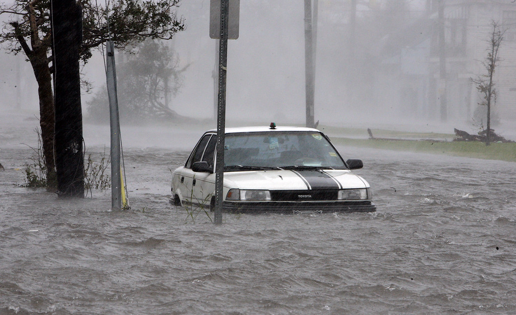 . Floodwaters surround a car in downtown New Orleans early Monday, Aug. 29, 2005 as high winds and rain batter the Louisiana coast as Hurricane Katrina made landfall.  (AP Photo/Bill Haber)