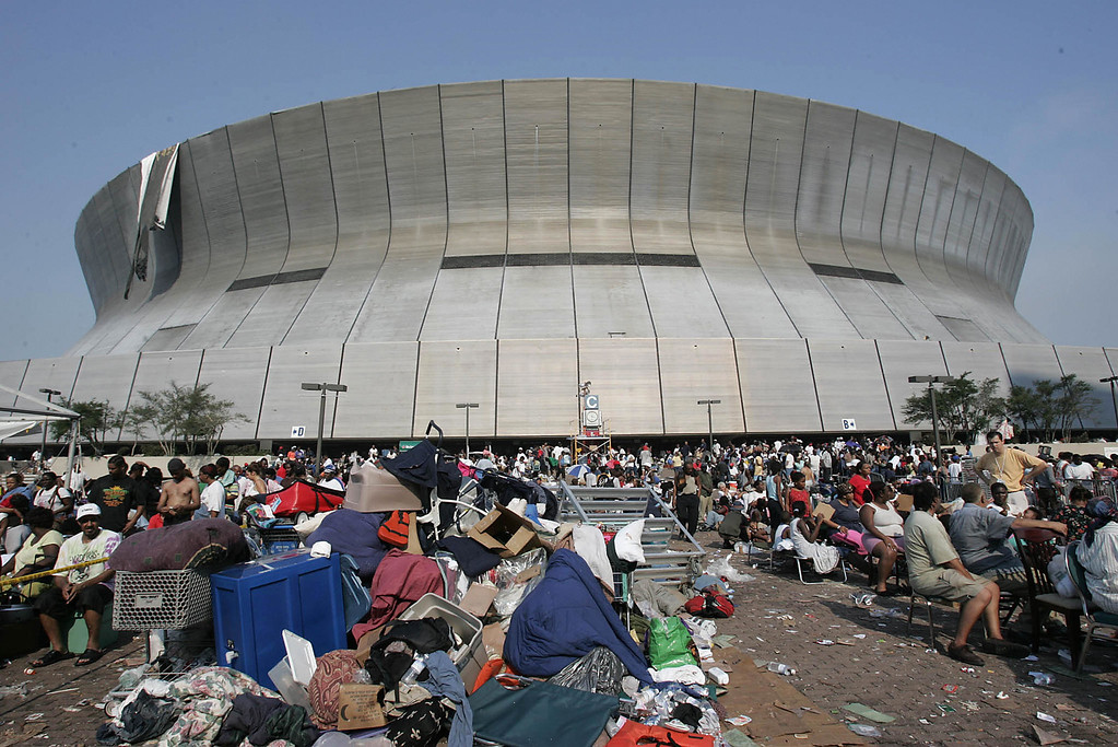 . Hurricane Katrina survivors wait outside the Superdome and Convetion Center in New Orleans 02 September, 2005. The New Orleans sports arena that housed hurricane refugees for five days in lawless squalor was finally emptied Friday, though many remained stranded with no immediate prospect of evacuation. While relieved to leave the confines of the Superdome, where many testified to pitch-dark nights of gunfire, rioting and rape, the evacuees found the devastated city outside offered little in the way of comfort.   (JAMES NIELSEN/AFP/Getty Images)