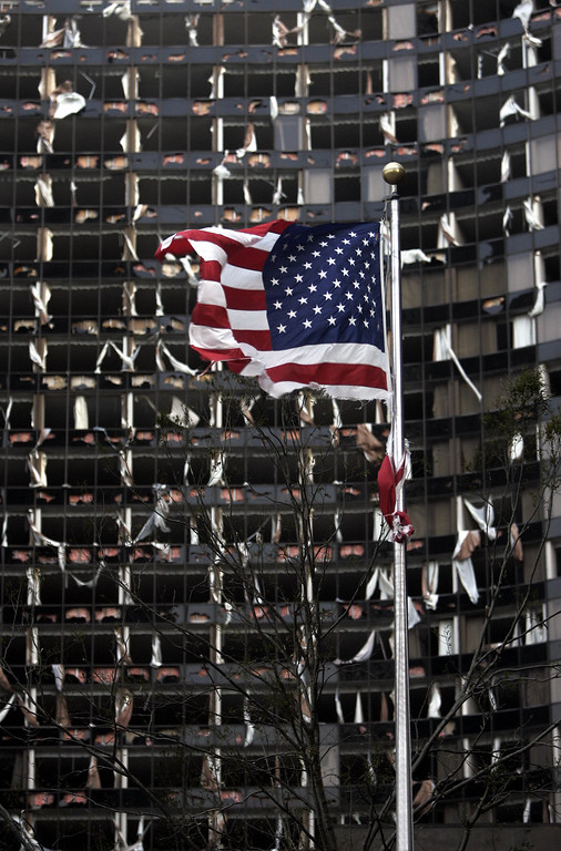 . A tattered U.S. Flag flies in the foreground of the Hyatt, in New Orleans, Monday, Aug. 29, 2005, where dozens of windows were blown out when Hurricane Katrina made land fall. ( (AP Photo/Eric Gay)