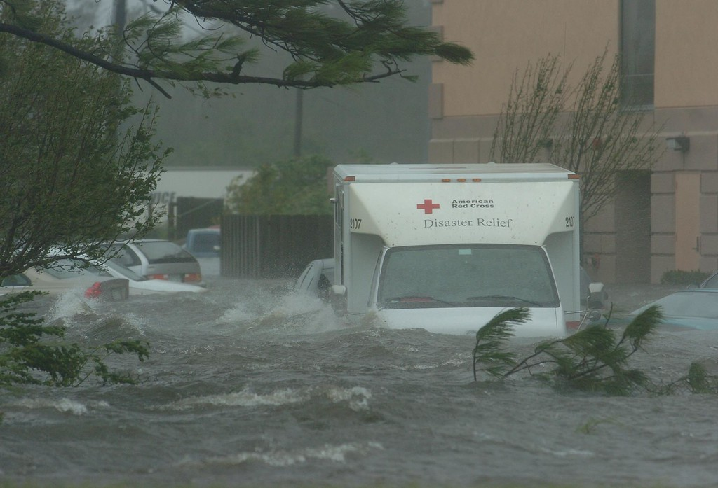 . A Red Cross truck sits flooded with other vehicles in front of a hotel just off Interstate 10 in Pascagoula, Miss., as Hurricane Katrina batters the area, Monday, Aug. 29, 2005. (AP Photo/Tampa Tribune, Michael Spooneybarger)