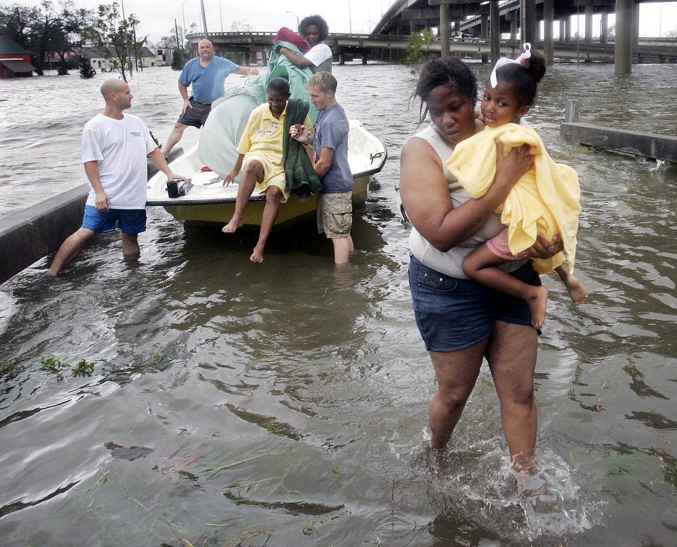 . Shante Gruld carries Janeka Garner, 5, to safety after they were rescued from their flooded home by boat  in  New Orleans,  Monday Morning, Aug. 29,  2005. The area was flooded after Hurricane Katrina hit the area. Officials had  called for a mandatory evacuation of the city, but many resident remained in the city.  (AP Photo/Eric Gay)