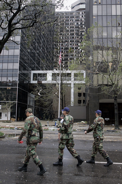 . Louisiana National Guard troops patrol past the blown out Hyatt Hotel in New Orleans on Monday, Aug. 29, 2005. Hurricane Katrina battered New Orleans with heavy rains and 140mph winds. (AP Photo/Bill Haber)
