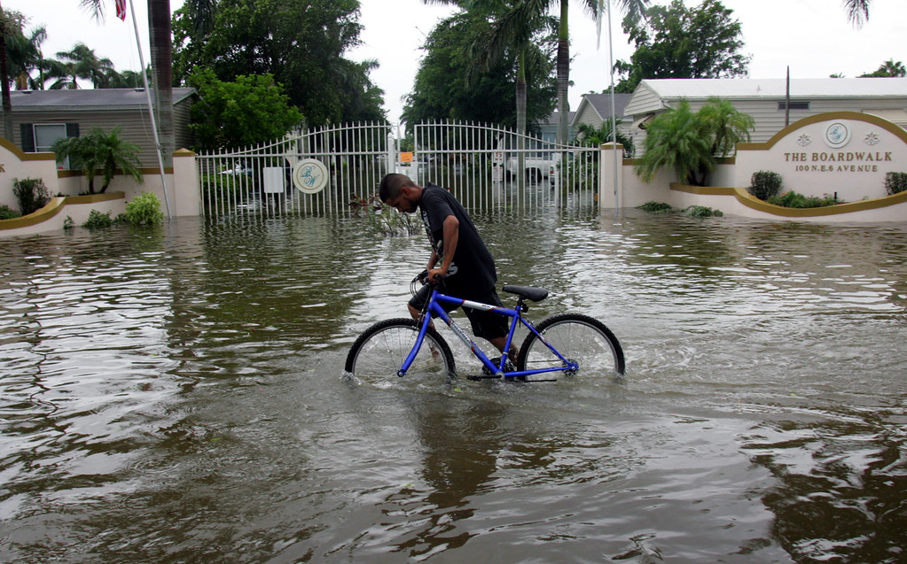 . Noe Morua pushes his bike past a flooded mobile home park in Homestead, Fla., Friday, Aug. 26, 2005. Hurricane Katrina flooded streets, darkened homes and felled trees as it plowed across South Florida before emerging over the Gulf of Mexico. (AP Photo/Luis M. Alvarez)