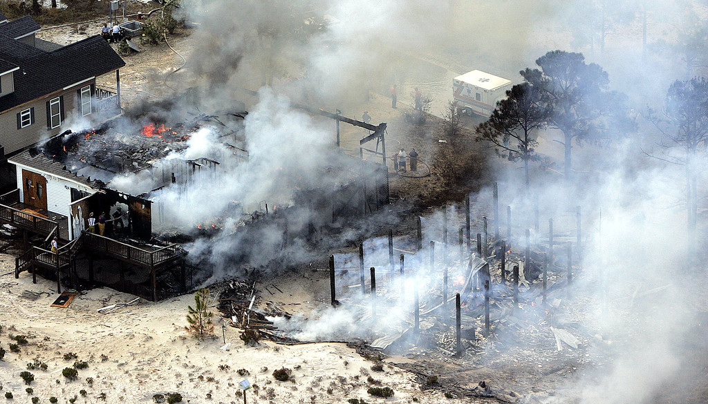 . Two homes burn out of control on Dauphin Island, Ala., Thursday, Sept. 1, 2005, after Hurricane Katrina passed through the area on Monday. (AP Photo/Phil Coale)