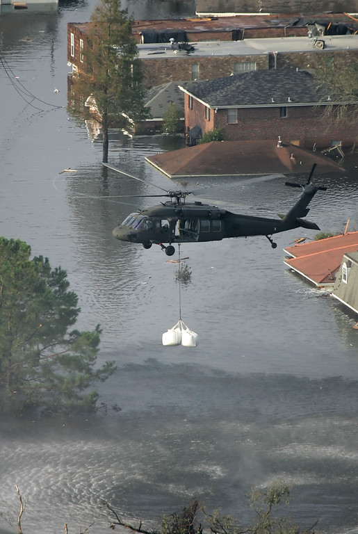 . A helicopter drops sandbags to fill a broken section of a levee which broke allowing floodwaters from Hurricane Katrina to fill the streets Thursday, Sept. 1, 2005 in New Orleans. (AP Photo/David J. Phillip)