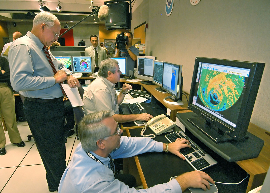 . National Hurricane Center Director Max Mayfield, left, checks his watch as hurricane specialist Stacy Stewart, right, makes the landfall call of Hurricane Katrina Monday, Aug. 29, 2005, at the National Hurricane Center in Miami. Katrina made its Gulf coast landfall at Plaquemines Parrish, La., just south of Buras at about 7:10 a.m. EDT. (AP Photo/Andy Newman)
